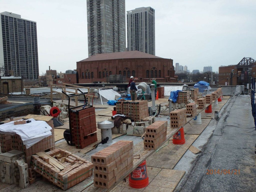 materials staged atop a commercial roof for replacement