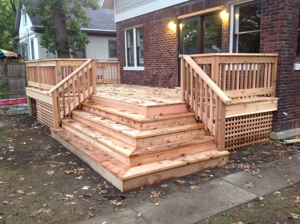 wooden back deck with corner steps and surrounding rails