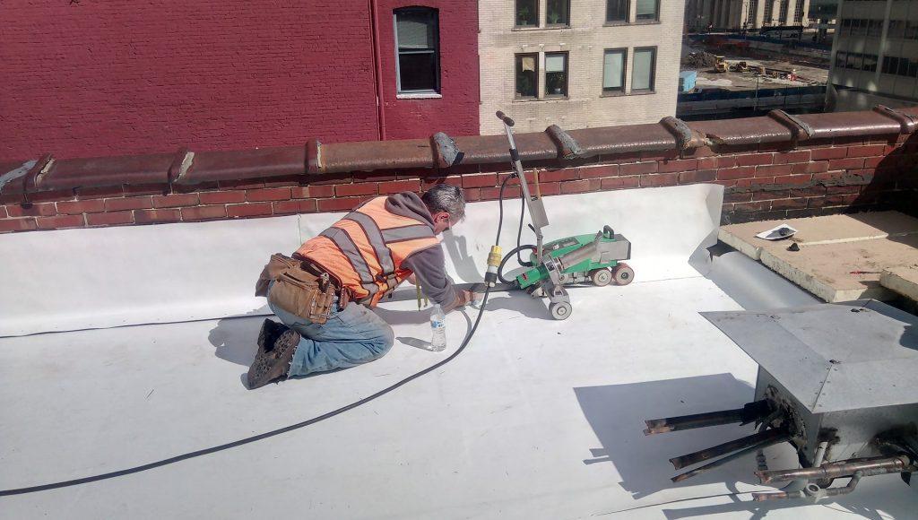 sealing membrane seam where flashing meets roof at parapet